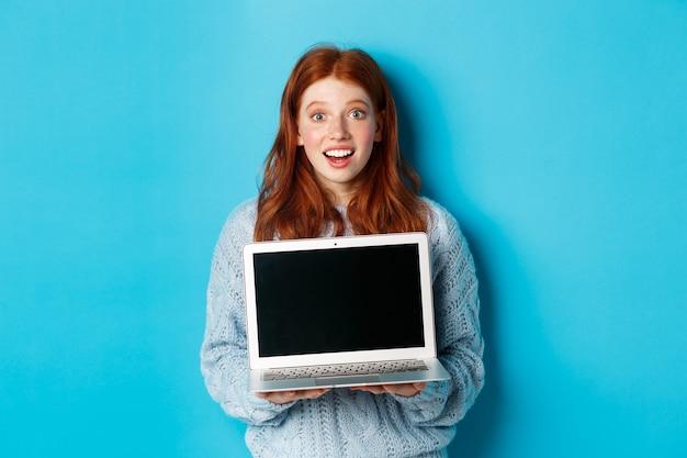 ノートパソコンの画面を表示し、驚いてカメラを見つめ、青い背景に対してコンピューターで立っている興奮した赤毛の女性フリーランサー