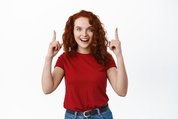 Взволнованная рыжая девушка объявляет о мероприятии, указывая пальцами вверх и счастливо улыбаясь, демонстрирует сверху, стоя в футболке у белой стены