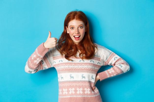 엄지 손가락으로 그녀의 지원을 보여주는 흥분된 빨간 머리 소녀 기쁘게 웃 고, 승인에 예, 동의, 파란색 배경 위에 서.