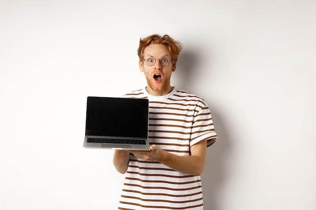 노트북 화면 로고 또는 웹 사이트를 보여주는 흥분된 빨간 머리 남자 드롭 턱, 흰색 배경에 서있는 디스플레이에 프로모션 제안을 보여줍니다.