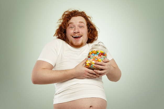 Excited redhead plump overweight man feeling happy after having found jar of tasty goodies