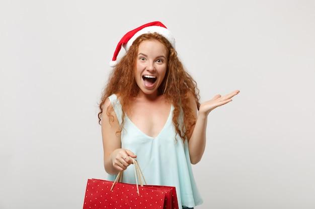 白い背景で隔離のクリスマス帽子で興奮した赤毛のサンタの女の子。明けましておめでとうございます2020年のお祝いの休日のコンセプト。コピースペースをモックアップします。買い物の後にギフトや購入品が入ったパッケージバッグを持ってください。
