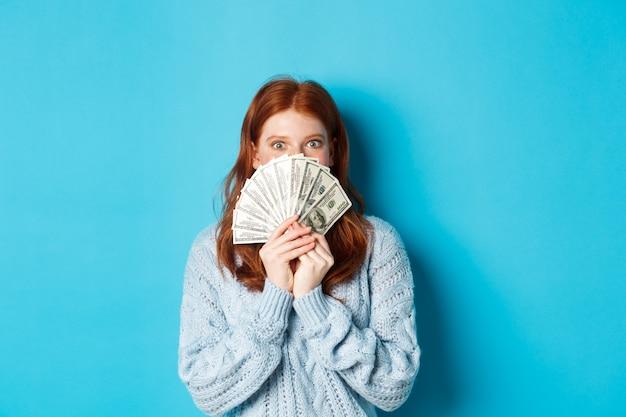 興奮した赤毛の女性は、お金で顔を覆い、ドルを保持し、青い背景の上に立って、幸せなカメラを見つめています。