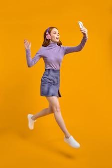 Возбужденная рыжая женщина в наушниках прыгает, гуляет и разговаривает по телефону онлайн через камеру, здоровается ...