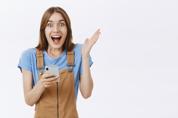 オンラインで素晴らしいニュースに反応し、スマートフォンを持って魅了されているように見える興奮した喜びの美しい少女