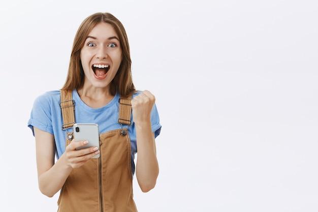 Возбужденная радость, красивая девушка реагирует на потрясающие новости в интернете, держит смартфон и выглядит очарованным