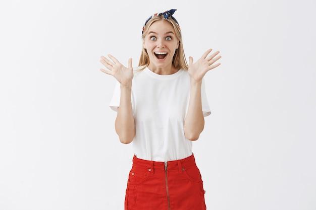 Giovane ragazza bionda eccitata e gioiosa in posa contro il muro bianco