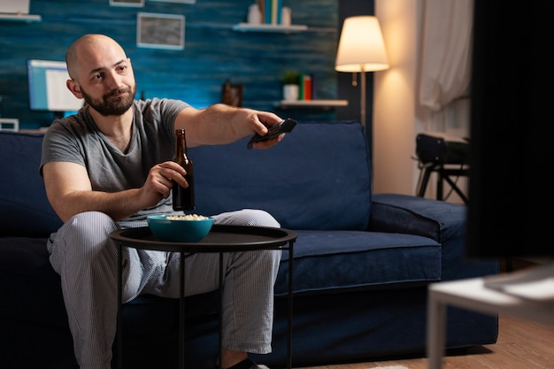 Excited relaxed man spending free time watching tv entertainment series