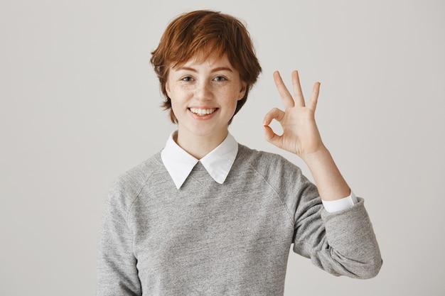 Ragazza rossa eccitata e soddisfatta con taglio di capelli corto in posa contro il muro bianco
