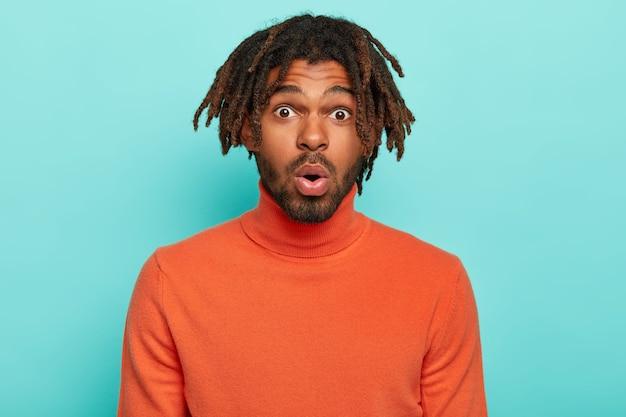 Eccitato uomo afro spaventato con i dreadlocks, indossa un dolcevita arancione, tiene la bocca aperta, reagisce alle notizie scioccanti dell'interlocutore