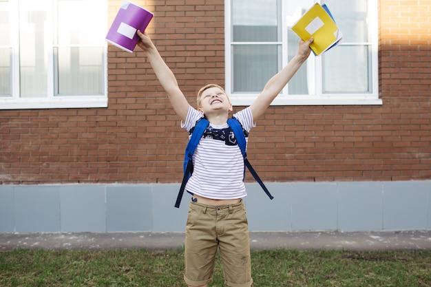 Взволнованный школьник держит тетради