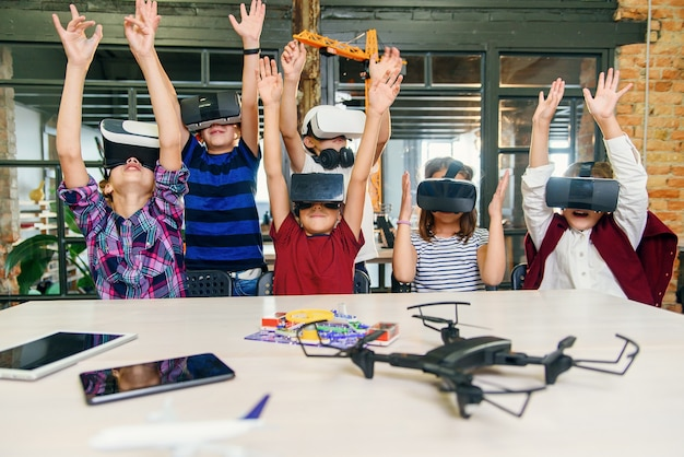 Возбужденные школьники современной умной начальной школы используют дополненную реальность для изучения новых технологий.