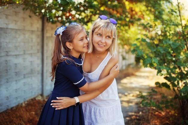 Возбужденная школьница обнимает маму