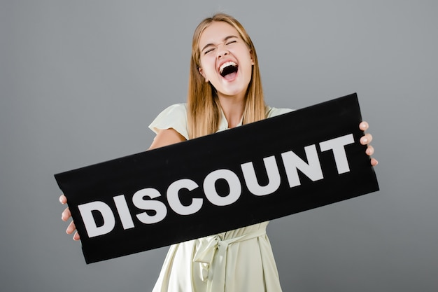 Excited screaming beautiful woman has discount sign isolated over grey