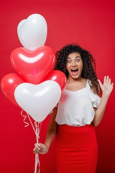 Excited screaming black woman with heart shaped red and white balloons isolated