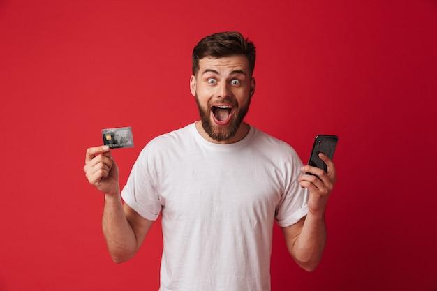 携帯電話とクレジットカードを保持している若い男を叫んで興奮。カメラを探しています。