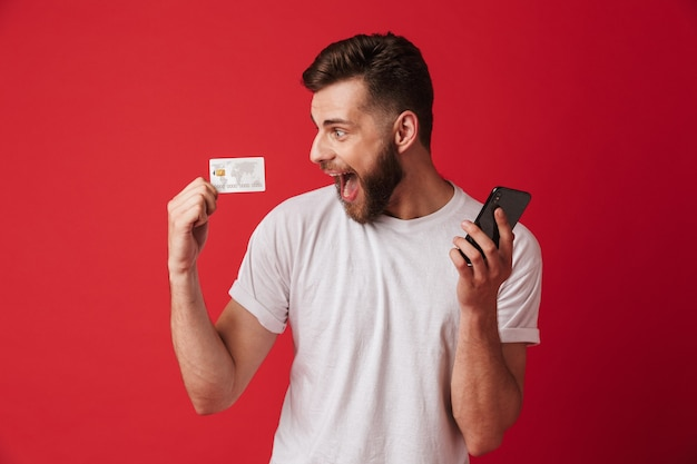 Excited screaming young man holding mobile phone and credit card. looking aside.