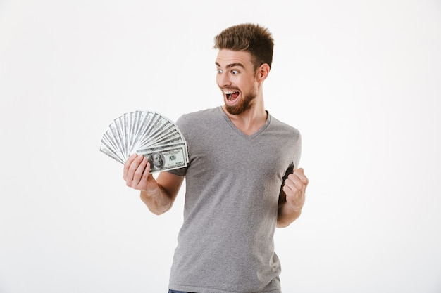 Возбужденный крик молодой человек, держащий деньги, делает жест победителя.