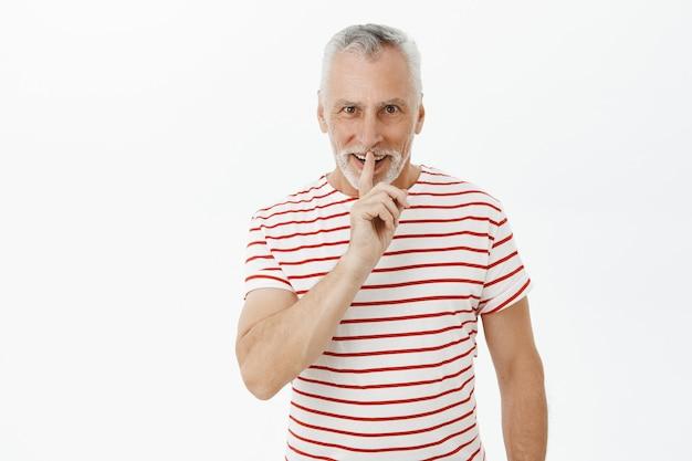 Uomo barbuto anziano eccitato che zittisce e sorride divertito