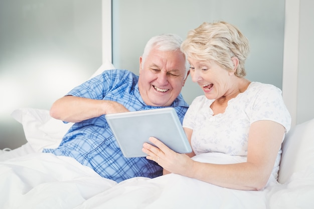 Excited senior couple using digital tablet on bed