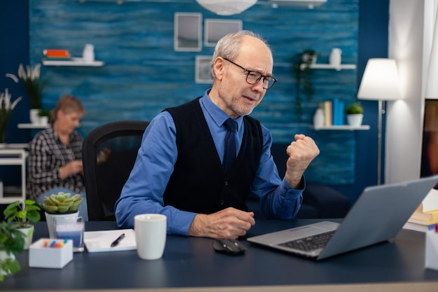 ホームオフィスからラップトップで作業しながら良いニュースを祝う興奮した年配の男性。妻が本を読んでいる間机に座ってポータブルコンピュータを使用して自宅の職場で老人起業家シッティ