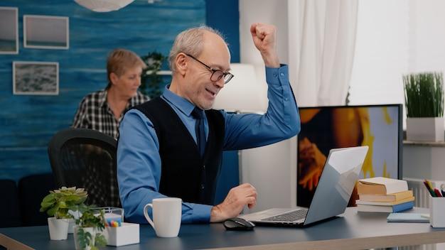 Возбужденный старший мужчина чувствует себя в восторге, читая отличные онлайн-новости на ноутбуке, работая из дома. пенсионер, использующий современные технологии, читает, печатает, ищет, пока старшая жена сидит на диване