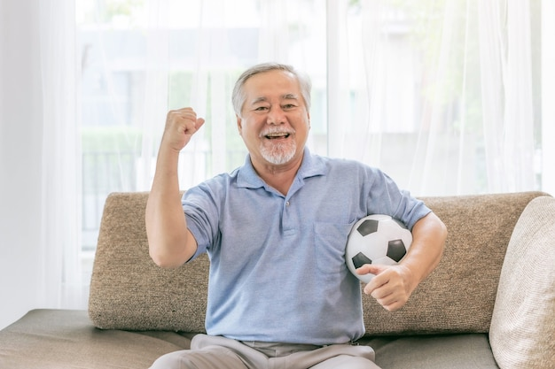 Excited senior man , old man feel happy holding football soccer ball prepare for cheer team favorite  on couch sofa at home , lifestyle asian senior good health concept