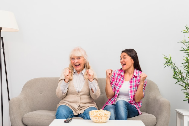 Excited senior mother and adult daughter sitting on sofa clenching their fist while watching television