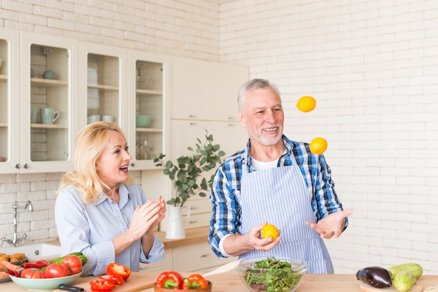 Excited senior woman clapping while her husband juggling lemons in the kitchen