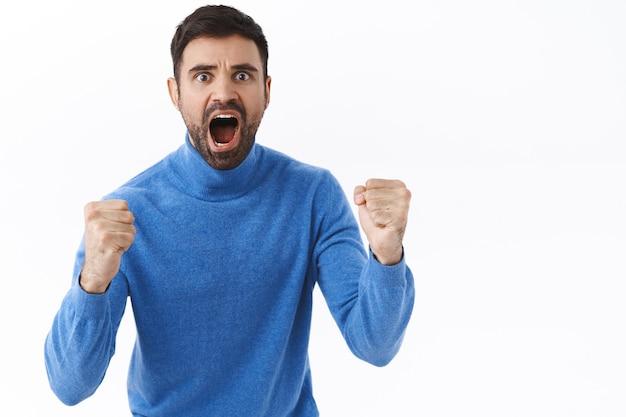 Взволнованный, серьезного вида энергичный молодой человек сделал ставку на футбольный спортивный матч, сжал кулаки и кричал, болел за команду, скандировал, глядя на экран телевизора, хотел, чтобы команда забила гол, белая стена