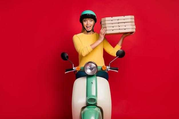Возбужденная шокированная девушка-студентка-курьер едет на велосипеде и доставляет коробку для пиццы на красной стене