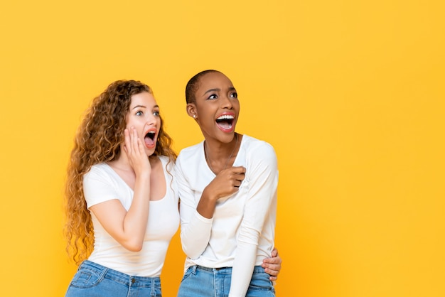 Excited shocked interracial woman friends looking aside isolated on yellow wall