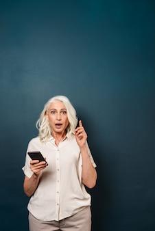 携帯電話を使用して興奮してショックを受けた成熟した老婆