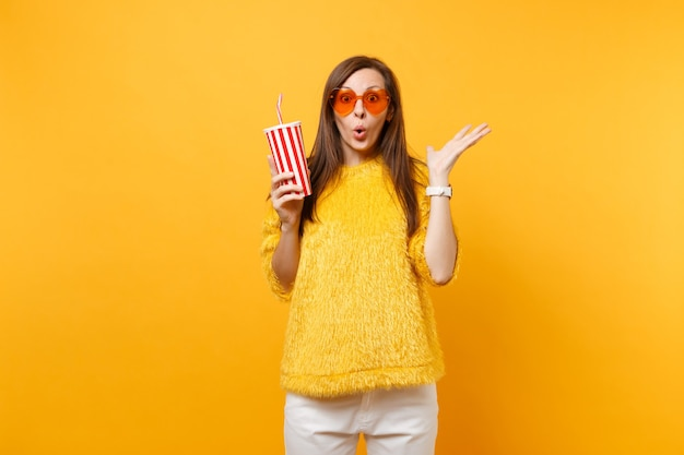 Excited shocked young woman in heart orange glasses spreading hands, holding plastic cup with cola or soda isolated on yellow background. people sincere emotions, lifestyle concept. advertising area.