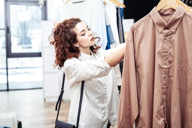 흥분된 쇼핑 중독. 퇴근 후 쇼핑하는 동안 진정으로 행복하고 흥분된 검은 눈의 곱슬 여자