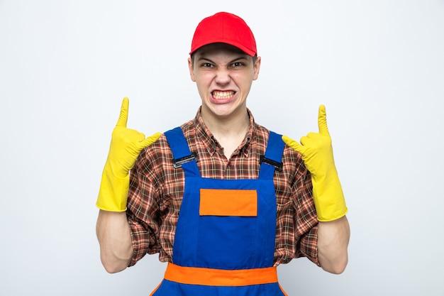 Eccitato che mostra il gesto di capra giovane ragazzo delle pulizie che indossa l'uniforme e il berretto con i guanti