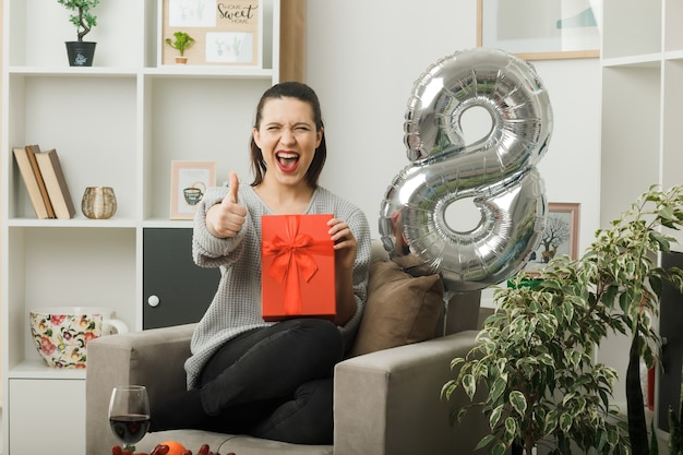 Excited showing thumb up beautiful woman on happy women day holding present sitting on armchair in living room