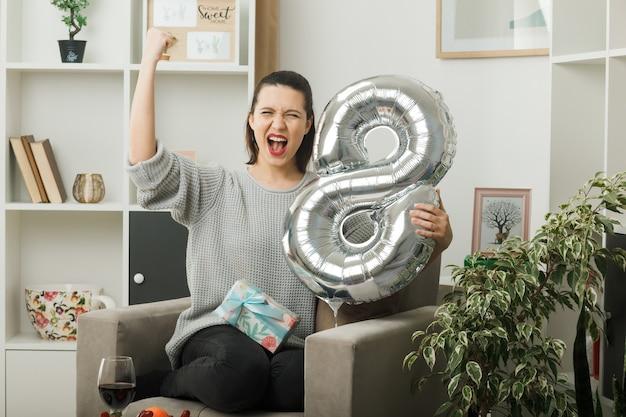 リビングルームのアームチェアに座って8番の風船を持って幸せな女性の日にイエスジェスチャー美しい女性を示す興奮