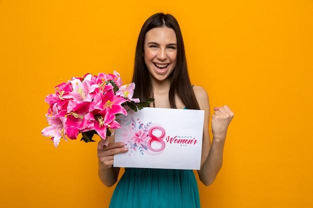 Eccitato che mostra sì gesto bella ragazza il giorno delle donne felici che tiene biglietto di auguri con bouquet