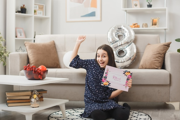 Excited showing yes gesture little girl on happy woman's day sitting on floor holding postcard in living room