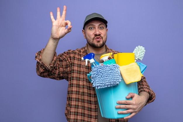 Eccitato uomo delle pulizie slavo che tiene in mano l'attrezzatura per la pulizia e che fa un gesto ok segno