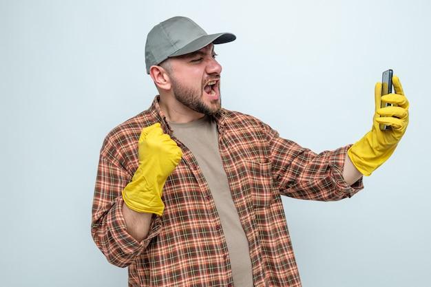 Eccitato uomo delle pulizie slavo con guanti di gomma che tiene il pugno e guarda il telefono