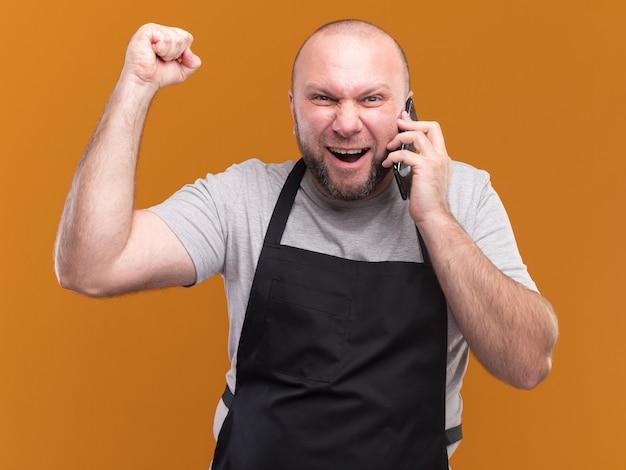 제복을 입은 흥분된 슬라브 중년 남성 이발사는 오렌지 벽에 고립 된 예 제스처를 보여주는 전화로 말합니다.