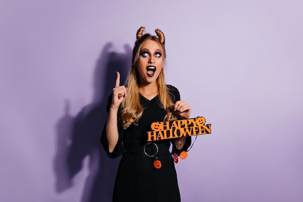 Excited slim girl waiting for halloween. enthusiastic blonde woman preparing for party.