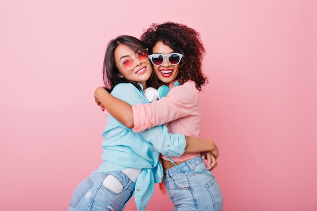 Возбужденная стройная девушка с африканской прической обнимает азиатскую подругу в модных ярких солнцезащитных очках. довольно европейская дама в джинсах обнимает черную молодую женщину в розовой рубашке.