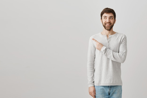 Excited smiling bearded guy pointing finger upper left corner