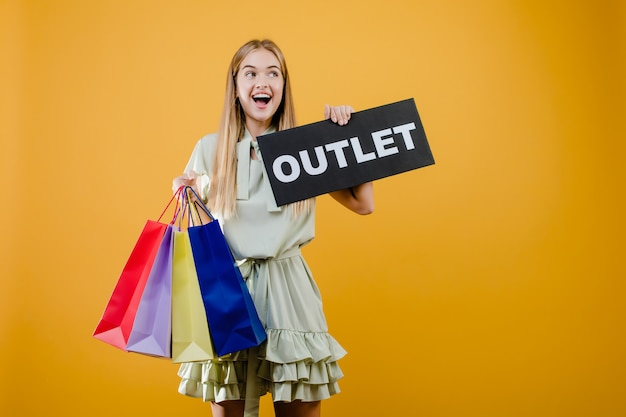 Excited smiling beautiful girl has outlet sign with colorful shopping bags isolated over yellow