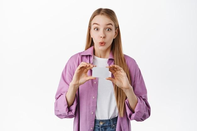 Eccitata ragazza bionda sorridente, sembra incuriosita davanti, mostrando la carta di credito della banca copyspace, in piedi sul muro bianco