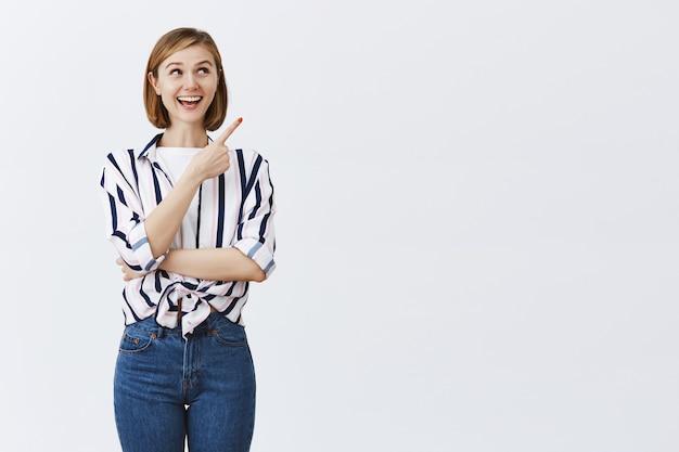 Взволнованная улыбающаяся милая женщина, указывающая в правом верхнем углу