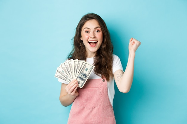 Excited smiling girl fist pump and hold money prize, winning cash, receive income from something, standing happy against blue background.